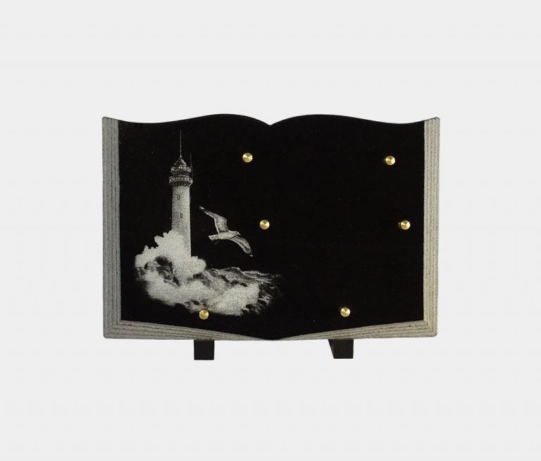 plaque funéraire moderne forme livre illustrée d'une gravure d'un phare